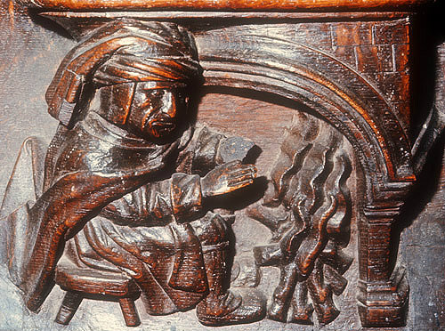 Misericord of labour of month of December, man warming himself by a fire, fifteenth century, Church of La Trinite, Vendome, France