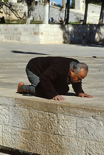 Israel, Jerusalem, Muslim man praying near the Dome of the Rock