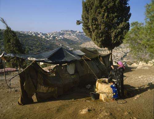 Bedouin woman at well by her tent with Bethlehem on the hill beyond, Israel