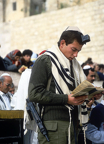 Israeli soldier carrying his gun whilst praying at the western wall