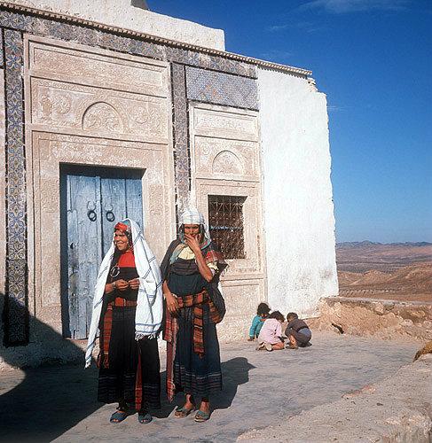 Two Berber women standing outside carved door of mausoleum, Takrouna, Tunisia