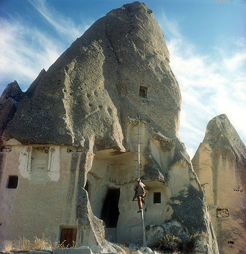 Cone dwelling with farmer climbing up to his pigeon loft on one pole ladder, Cappadocia, Turkey