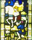 St Martin cutting cloak for a beggar, stained glass window 1918 by H Bryans, designed by Ernest Heaseman, Church of St Mary, Newton Valence, Hampshire, England, Great Britain