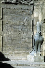 Egypt, Edfu, Temple of Horus, relief of Ptolemy giving gifts to the falcon god Horus, beside a black granite statue of Horus
