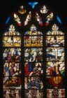 Crucifixion with donor Guy de Laval kneeling in centre light, 16th century stained glass, Church of St Martin, Montmorency, France