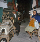 Old man and woman sitting outside a saddle shop in Kato Figalia, Aarcadia, Greece