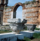 Byzantine style acanthus leaved capital, with Basilica behind showing alternate courses of brick and stone, Pbilippi, Greece