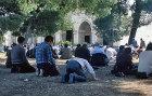 Israel, Jerusalem, Muslim men kneel for Friday prayer outside the Al Aqsa Mosque
