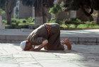 Israel, Jerusalem, Muslim man praying near the Dome of the Rock