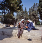 Israel, Jerusalem, two Arabs in deep conversation sitting on a wall in the Temple Area