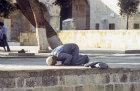 Israel, Jerusalem, Muslim man praying outside the Dome of the Rock