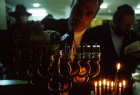 Israel Hanukkah Feast of Lights religious Jew fills Menorah with olive oil