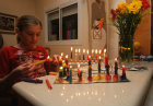 Israel Hanukkah girl lighting Menorah on the eighth day