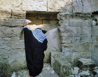 Israel, an Arab peering into a tomb with a rolling stone like Jesus