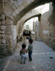 Israel, Jerusalem, donkey with water cans, tethered in the old city, and two small boys