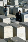Israel Jerusalem Orthodox Jews pass by graves in the Jewish Cemetery on the Mount of Olives