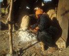 Woman preparing fire in clay oven, Jordan