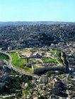 North end of the L-shaped Citadel, with Bronze and Iron Age walls, eighth century Umayyad complex, surrounded by modern city, aerial, Amman, Jordan