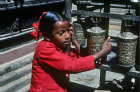 Girl turning prayer wheels, Patan, Nepal