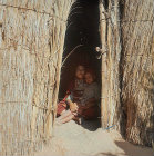 Berber woman and child in doorway of bamboo dwelling, Island of Djerba, Tunisia