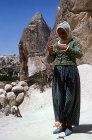 Girl spinning wool  outside cone dwelling Cappadocia, Turkey