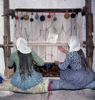 Girls working at a loom in a cone dwelling, Cappadocia, Turkey