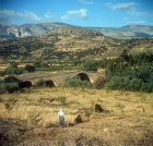 Workers in the fields, Taurus mountains behind, and Selcuk bridge, Cilicia, Turkey
