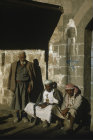 Yemen, Wadi Dahr, men sitting in the sun