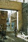 Child beside doorway of house in Sana
