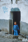 Child in doorway of house, Sana